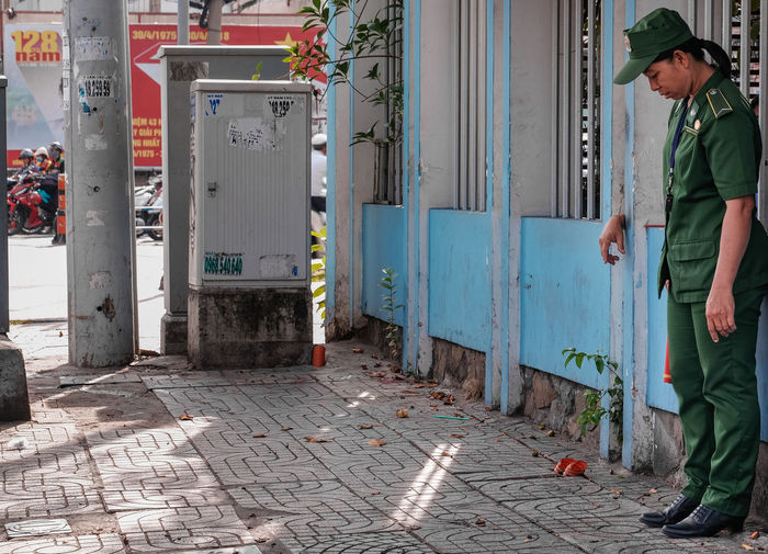 Man standing on footpath by street