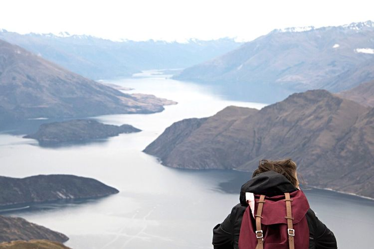 Person with backpack against river and mountains