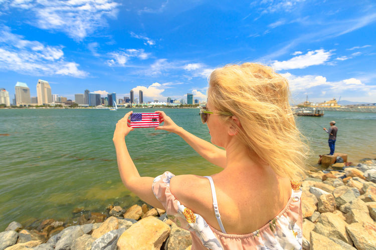 Blonde happy tourist takes photo of San Diego By skyline by mobile phone with American flag cover. Woman lifestyle takes picture in California summer holidays with smartphone from Coronado Island, USA United States America American American Flag Woman People Female Girl California San Diego San Diego, California Beach Sea Seascape Skyline Cityscape Shore Nature Vacations Holiday Summer Lifestyles Tourist Coronado Coronado Beach Coronado Island Water Sky One Person Real People Leisure Activity Built Structure Architecture Women Building Exterior Adult Young Adult City Hair Cloud - Sky Day Outdoors Hairstyle Office Building Exterior