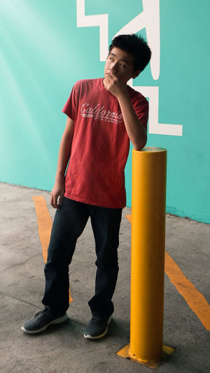 Young man thinking while leaning on bollard while standing on footpath against wall