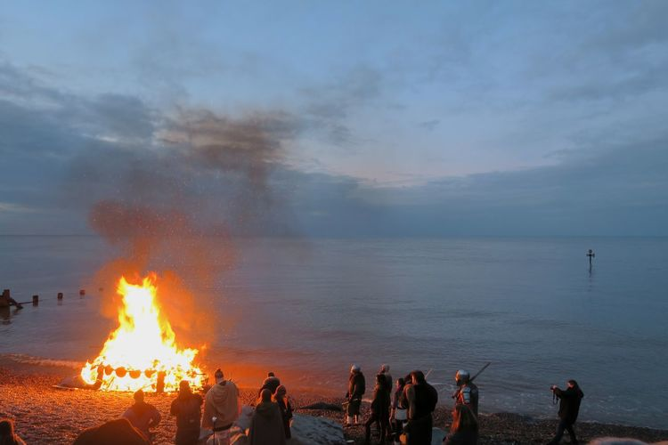 People by campfire at beach against sky