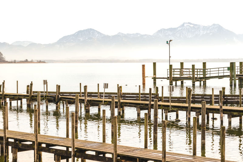 Water Beauty In Nature Lake Sky Scenics - Nature Wooden Post No People Nature Day Outdoors Tranquility Calm Mountain Fog Chiemsee Dock Landing Stage Reflection