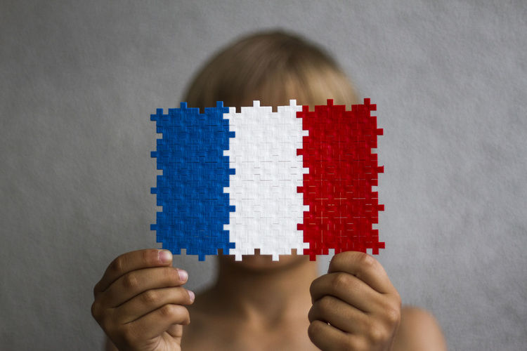 Boy Covering Face With Flag Pattern Paper Against Wall
