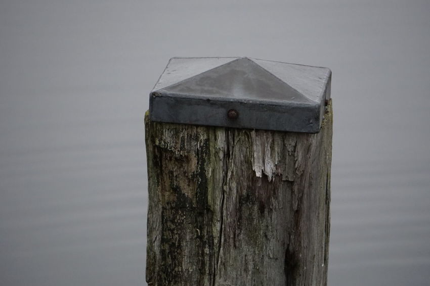 Bollard Wood - Material No People Day Nature Outdoors Focus On Foreground Close-up Birdhouse Tranquility Post Gray Tranquil Scene Built Structure Wooden Post Architecture Old Beauty In Nature Lake Environment Detail Bollard