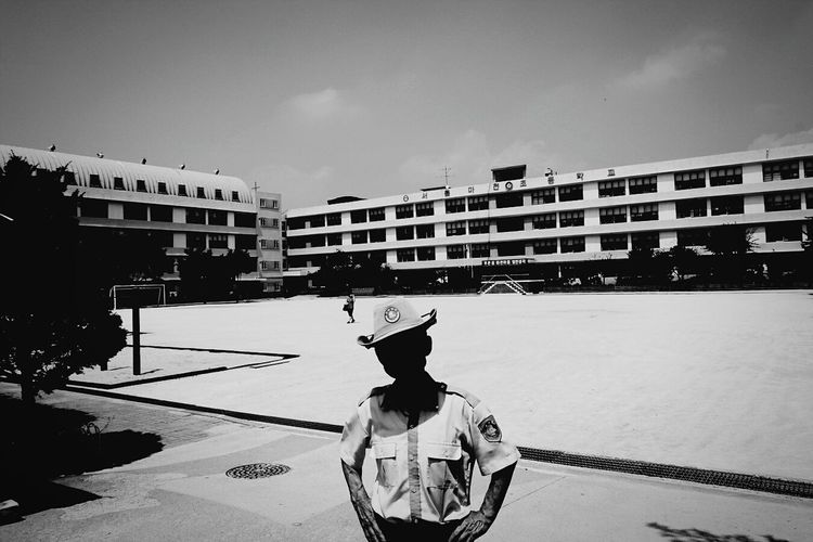 Security Guard Standing With Hand On Hip Against Buildings And Sky