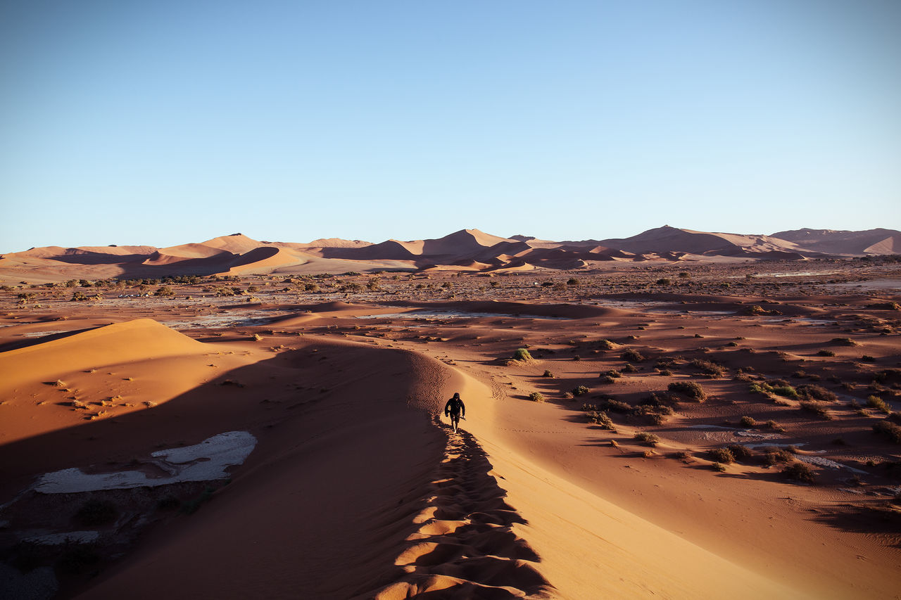 High angle view of person on sand dune at namib desert against clear sky