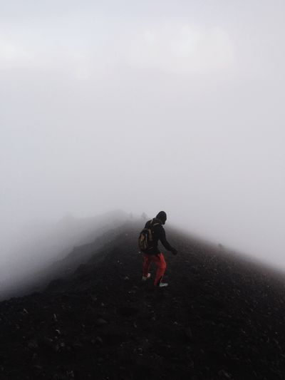 Rear view of man hiking on mountain in foggy weather
