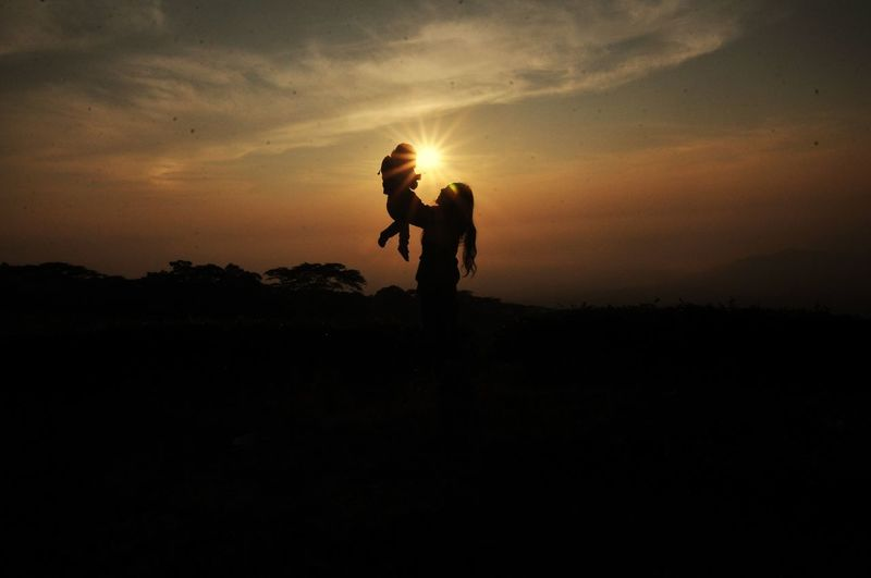 Silhouette woman picking up daughter against sky during sunset