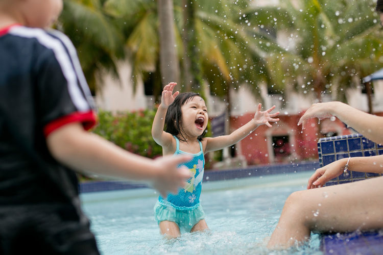 Asian little girl playing at swimming pool Swim Kid Toodler Asian  Girl Portrait Happy Summer Holiday Water Slide Water Friendship Child Spraying Swimming Pool Childhood Happiness Cheerful Togetherness Shouting Mouth Open Wet Hair Swimming Trunks