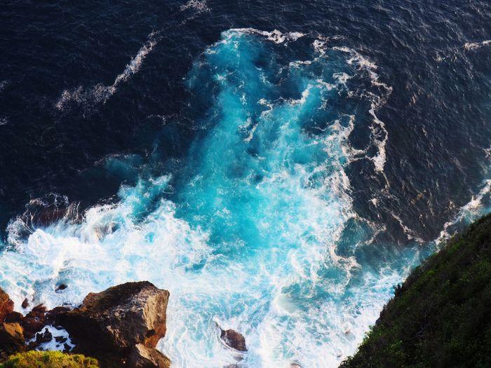 High angle view of waves splashing on rocks in sea