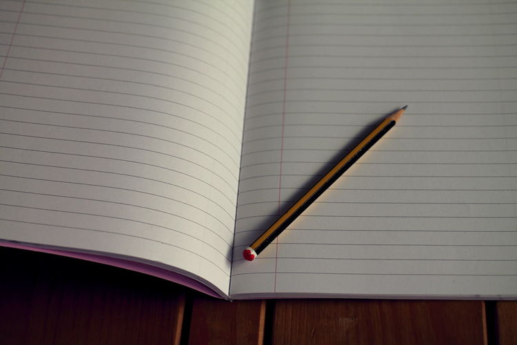 Close-up of book and pencil on wooden table