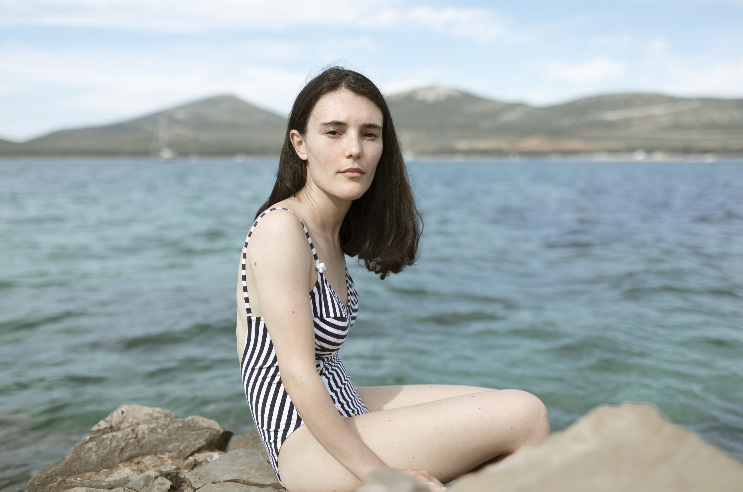 one person, water, lifestyles, leisure activity, young women, young adult, mountain, real people, beauty, women, beautiful woman, rock, sea, beauty in nature, rock - object, nature, day, outdoors, hairstyle