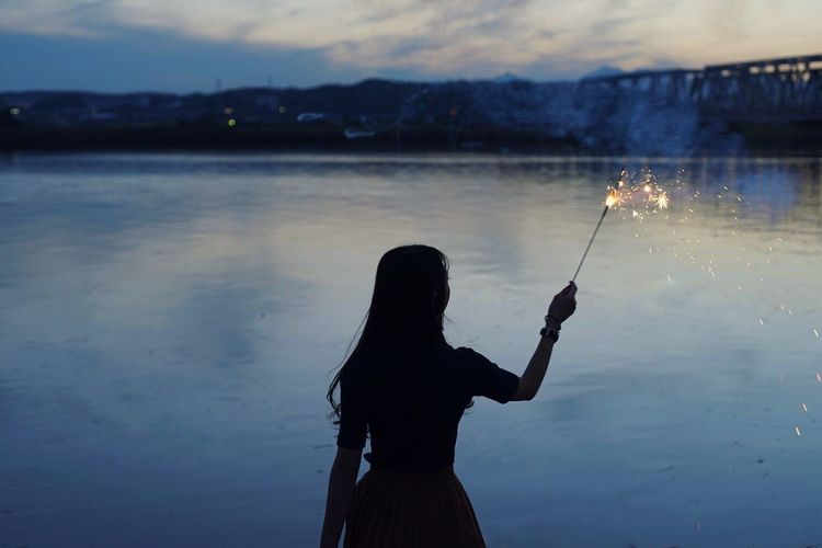 Silhouette Of Woman Standing By Lake Holding Sparkler