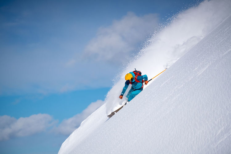 Man skiing on snowcapped mountain against sky