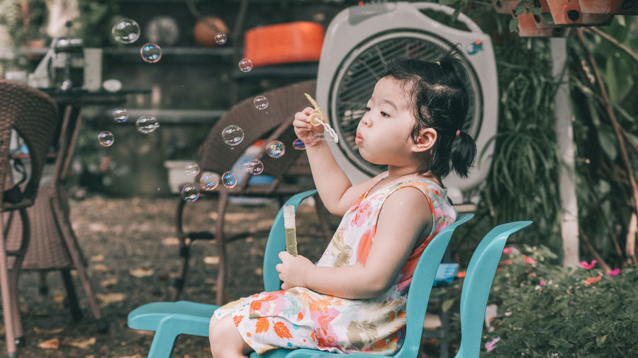 Full Length Of Cute Girl Blowing Bubbles While Sitting On Chair At Yard