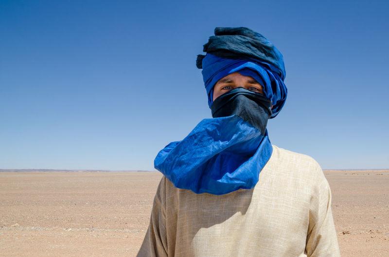 Portrait of man wearing headscarf at desert