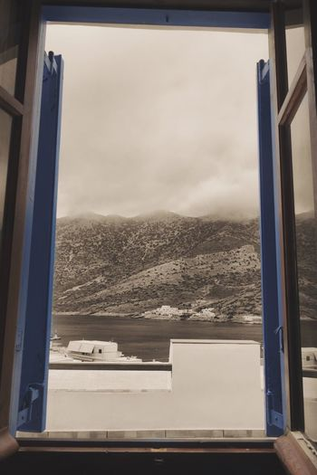 A window into the past Window Sky Sea Mountain Day Water Blackandwhite Colour And Black And White Eyemphotography Window View GREECE ♥♥ Bay Calm Beauty In Nature Scenics Nature Scenery Island Traditional Window Frame Window Reflections Overview History Historical Tradition