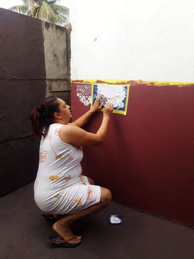 Side view of woman painting on wall