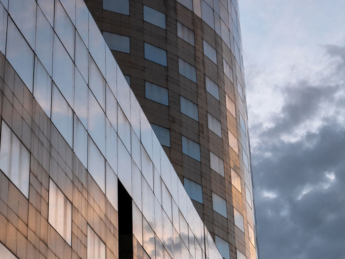 Part of office building in the sunset light with beautiful reflections of sunlight and clouds