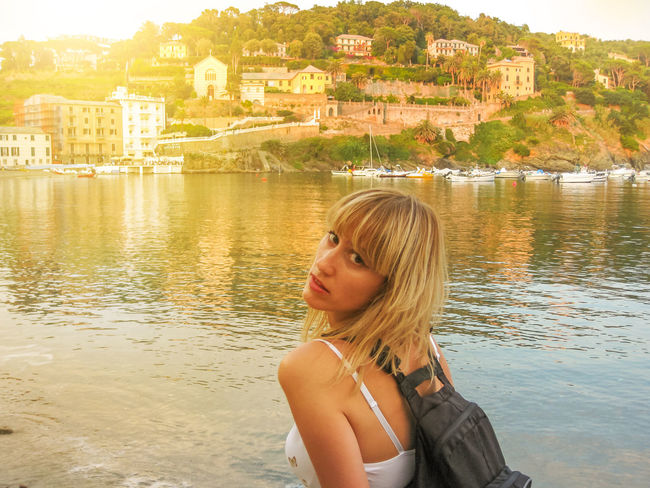 Italian young tourist posing at sunset. On the background the colorful houses of the popular tourist resort of Sestri Levante. Province of Genoa in Liguria, Italy. City Genova Sestri Levante Skyline Aerial View Baia Del Silenzio Bay Beach Beautiful Woman Beauty In Nature Boats Cistyscape Fishing Girl Italy Leisure Activity Lifestyles Liguria Marine Nature One Person Outdoors Real People Sea Seascape Ships Silence Sunset Town Village Water Waterfront Women Young Adult Young Women