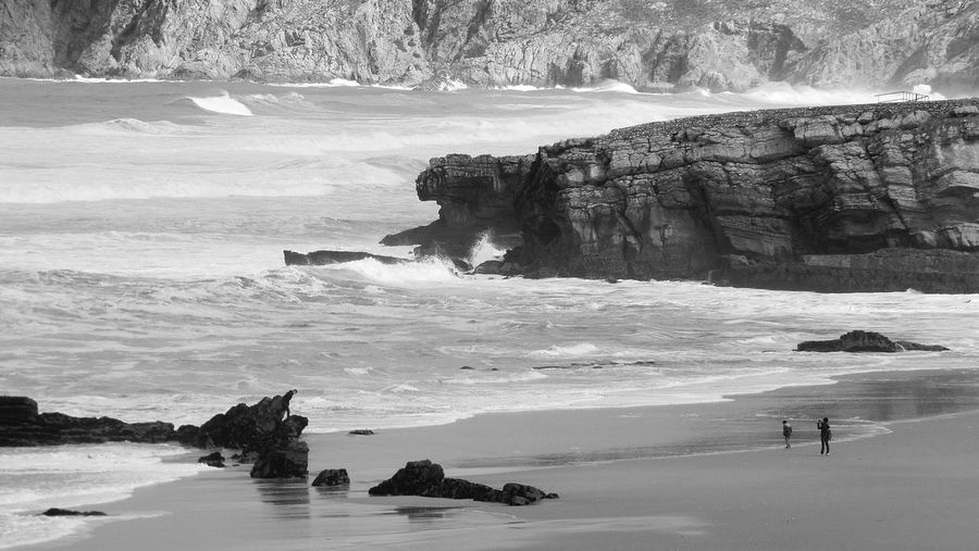 The Beach the Sea and the People Black & White Black And White Photography Seaside Water Rock Formation Rocks Eye4photography  EyeEm Gallery In this photo are 3 people a Woman and a Boy and a Man Look Better  Beach Photography Black And White Sea View