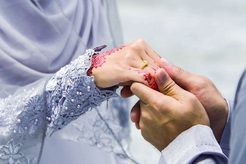 Cropped image of groom holding bride hand
