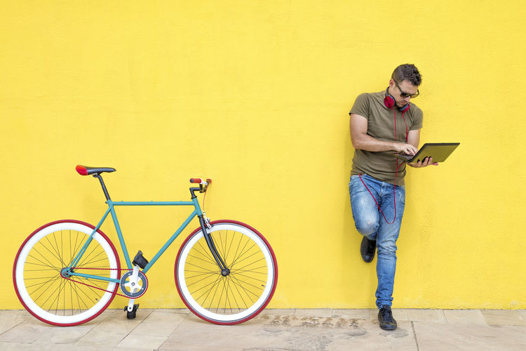 Front view of a young trendy man with a fixed bike wearing casual clothes while using a laptop standing against a yellow wall outdoors in sunny day Wall - Building Feature Full Length Young Adult Bicycle Casual Clothing Young Men Lifestyles One Person Real People Standing Transportation Yellow Front View Architecture Leisure Activity Holding Built Structure Looking Mode Of Transportation Young Man Hipster Trendy Fashionable Hat T-shirt