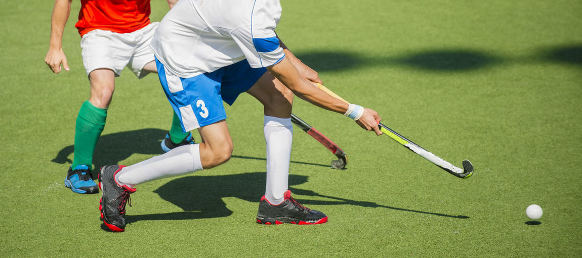 Low Section Of Men Playing Hockey On Turf