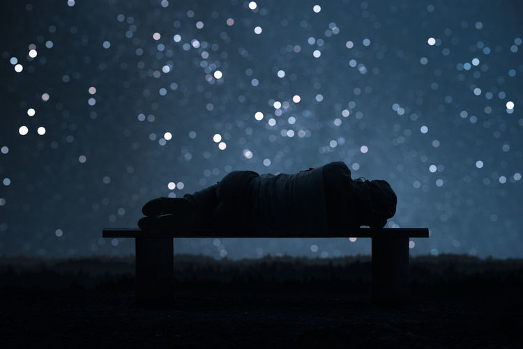Rear view of man sleeping on bench against sky at night