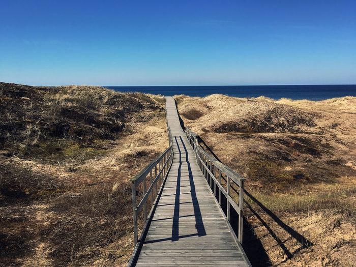 Boardwalk leading to sea against clear blue sky