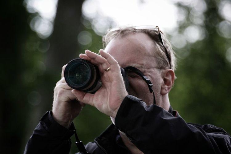 Close-up of mature man photographing through camera