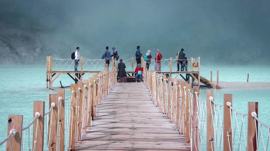 People On Pier Over Lake During Foggy Weather