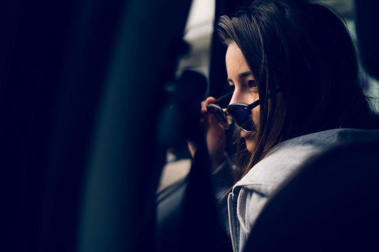 Teenage girl in sunglasses looking through car window