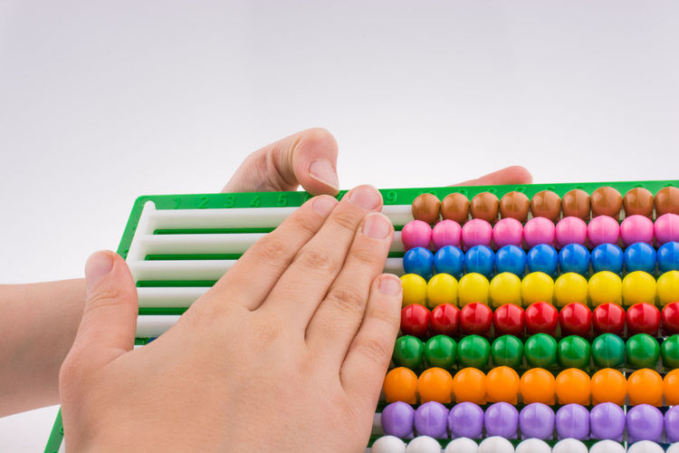 Cropped hands of child holding abacus against white background