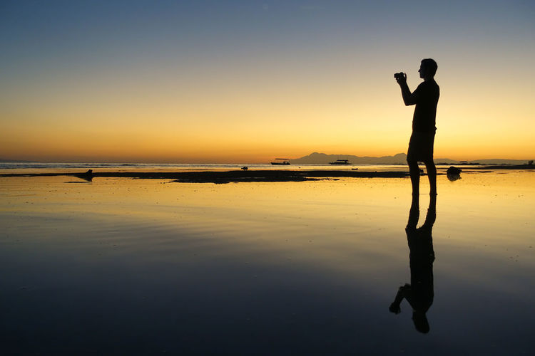 Photographer man and camera in a natural pool - silhouette at sunset Beach Sunrise Beach Sunset Digital Nomad Dslr Camera Horizon Island Sunset Island View  It's More Fun In The Philippines Man Philippines Photograper Silhouette Photographer Photographer Outline Profile Reflection Silhouette Still Water Sunrise Sunset Taking A Photo Taking A Picture Taking Pics Travel Wandering World Traveller