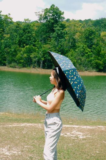 Woman standing by lake against trees