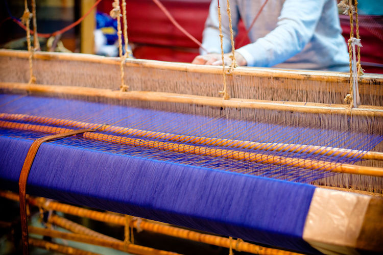 Midsection Of Man Working With Loom In Workshop