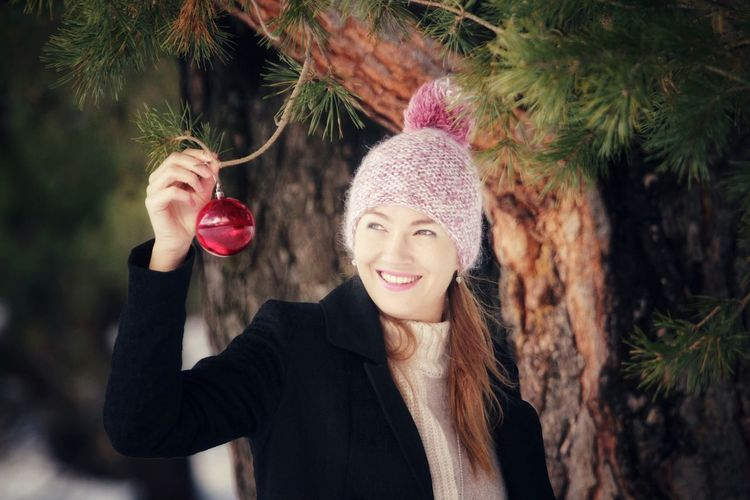 Smiling woman holding bauble by tree during winter