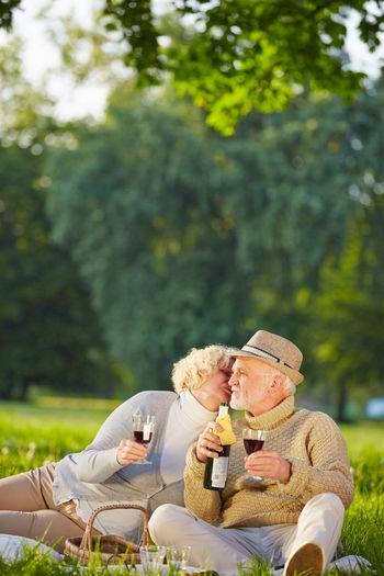 Senior Couple Having Wine While Sitting At Park