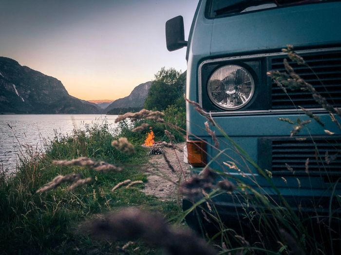 Camper Campfire Mood Fire VW Bus Plant Mode Of Transportation Transportation Nature Land Vehicle Sky Water No People Car Scenics - Nature Grass Land Beauty In Nature Tranquility Stationary Tree Outdoors Day Summer Road Tripping The Traveler - 2018 EyeEm Awards