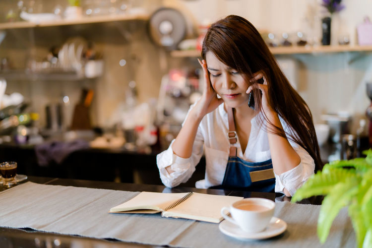 An asian barista woman is stressed because of economic conditions and covid-19