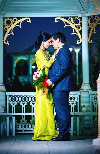Full length of newlywed couple standing in illuminated gazebo