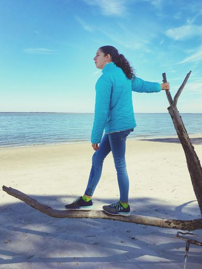 Side view of girl looking away while standing on branch at beach against sky