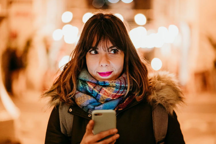 Portrait of woman holding smart phone during winter