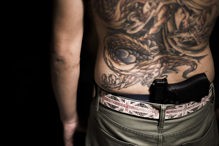 Midsection of tattooed man with gun in darkroom