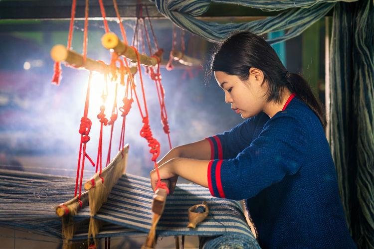 Side view of woman weaving loom in workshop