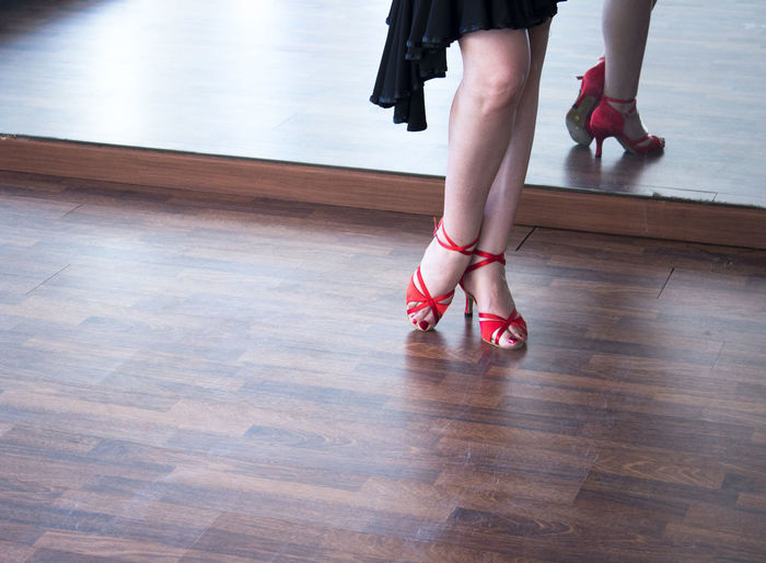 Low section of young woman wearing red high heels while standing on hardwood floor by mirror