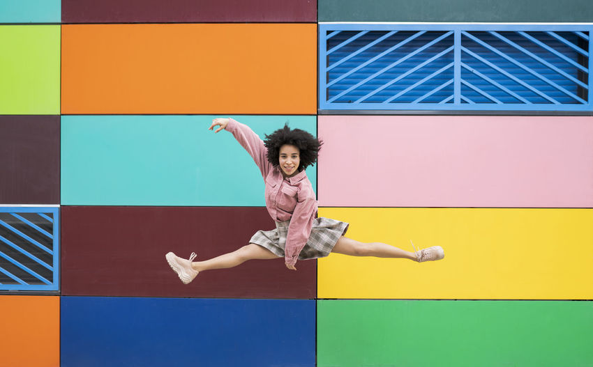 Full length of boy jumping against blue wall