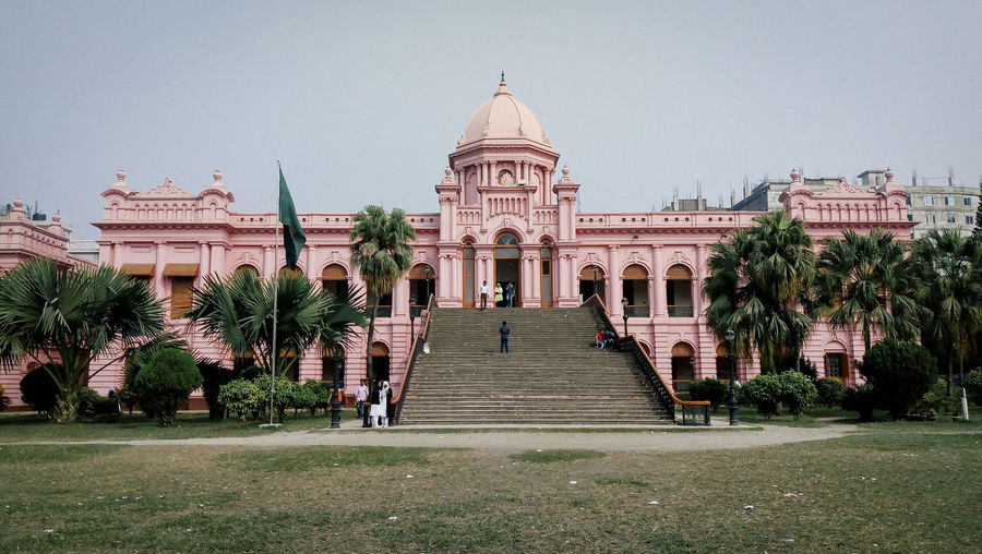 Ahsan Manzil, a beautiful pink palace along the Buriganga river in Dhaka, Bangladesh, that used to be the residence of the Nawab of Dhaka. ASIA Ahsan Manzil Bangladesh Bangladeshi Bengal Dhaka India Millenial Pink Old Dhaka Tropics Architecture Building Exterior Clear Sky Dreamy Landscape Light Pink Palace Palace Garden Palm Trees Pink Color Tourism Travel Destinations