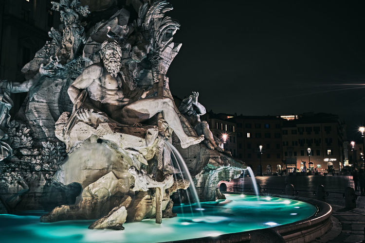 View of fountain in city at night